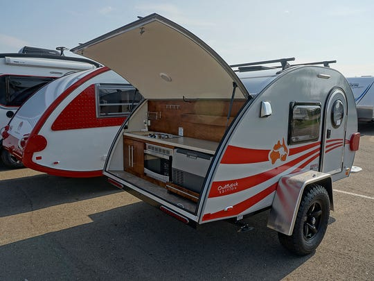The camper trailer includes a galley with a 2-burner stove, sink, fridge, and a microwave.