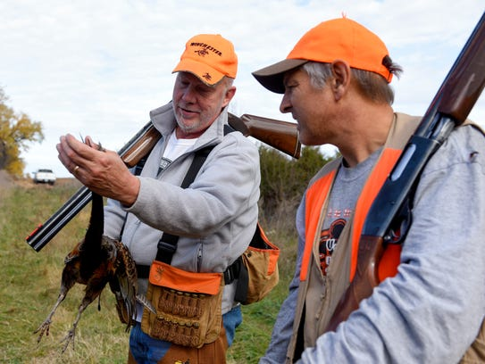 Brian Doering (left) shows a pheasant he shot on land