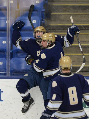 DCD's Dallas Hood celebrates scoring a goal in the second period with teammates Gino Sessa (4) and Harrison Dunbar.