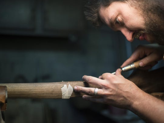 In this Sept. 8, 2016 photo, Nate Woltering of Columbus, Ohio, meticulously removes excess wood from the inside of his gun stock so that the trigger and magazine well will fit snuggly into the frame, inLivingston, Mont. Woltering is part of Steven Hughes' five day Professional Gun Stock Making class in Livingston. (Rachel Leathe/Bozeman Daily Chronicle via AP)