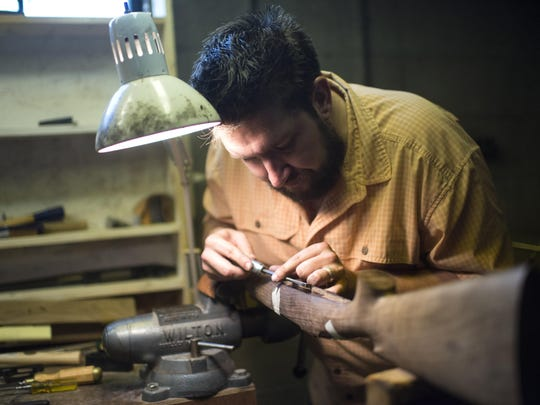 In this Sept. 8, 2016 photo, Nate Woltering of Columbus, Ohio, meticulously removes excess wood from the inside of his gun stock so that the trigger and magazine well will fit snuggly into the frame, in Livington, Mont.. Woltering is part of Steven Hughes' five day Professional Gun Stock Making class in Livingston. (Rachel Leathe/Bozeman Daily Chronicle via AP)