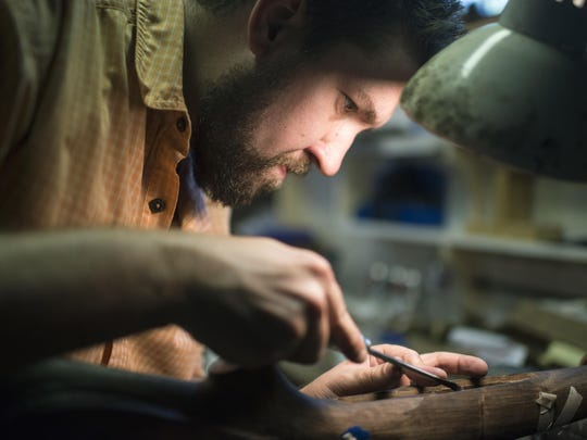In this Sept. 8, 2016 photo, Nate Woltering of Columbus, Ohio, meticulously removes excess wood from the inside of his gun stock so that the trigger and magazine well will fit snuggly into the frame, in Livingston, Mont. Woltering is part of Steven Hughes' five day Professional Gun Stock Making class in Livingston. (Rachel Leathe/Bozeman Daily Chronicle via AP)