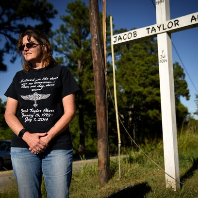Carol Akers stands at the location of the accident