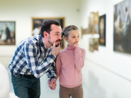 interested father and daughter regarding paintings in museum