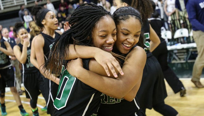 Ypsilanti Arbor Prep's Ro'Zhane Wells embraces her teammate Jasmine Henry after defeating Traverse City St. Francis 54-37 during the MHSAA girls basketball Class C finals at the Breslin Center in East Lansing on Saturday, March 19, 2016.