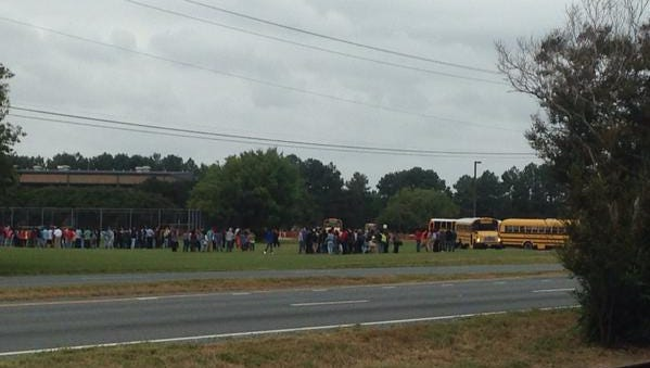 Students and staff line up outside the school during Friday's bomb threat.