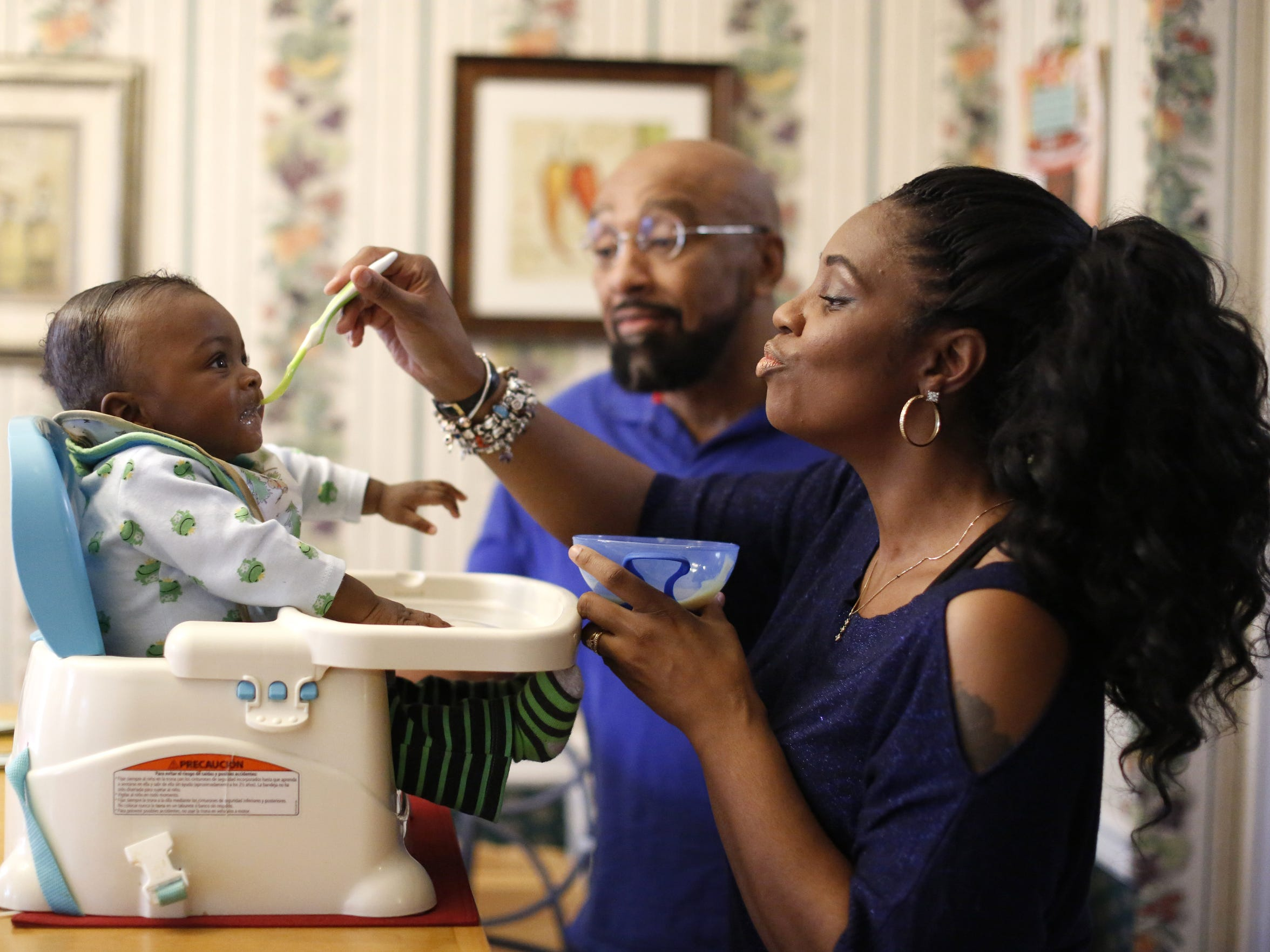 Lorraine Nichols feeds her seven-month-old son Caleb Charlie Nichols as her husband Charles stands by Dec 12.