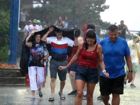 Drenched fans leave as Def Leppard performs at the American Family Insurance Amphitheater July 4.