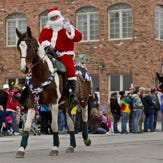 Santa waves to the crowd during the Old Fashioned Christmas Horse Parade.