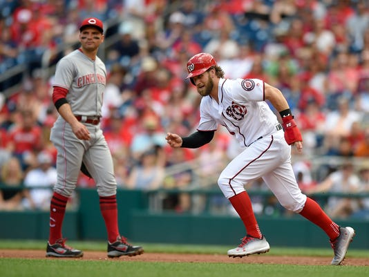 Washington Nationals' Bryce Harper, right, runs toward second base on a wild pitch past Cincinnati Reds first baseman Joey Votto, left, during the first inning of a baseball game, Sunday, June 25, 2017, in Washington. (AP Photo/Nick Wass)