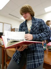 Student Andrew Marting scans through a school's yearbook Thursday at Wausau East High School.
