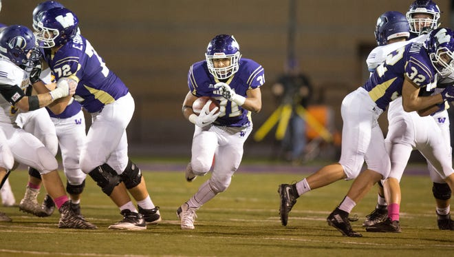 Waukee High School's Daniel Ray (31) runs through a hole in the Indianola line in the second quarter Friday, Oct. 9, 2015, at Waukee Stadium in Waukee.