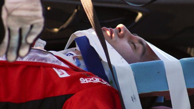 Matteo Malucelli is removed from his car after he was involved in a wreck during the IMSA Series Rolex 24-hour auto race at Daytona International Speedway on Jan. 25, 2014.