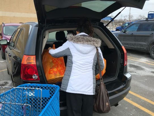 Crystal Hernandez loads up her vehicle with bags of
