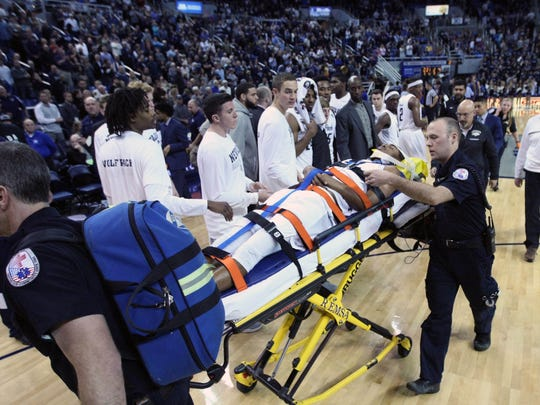 Wolf Pack Josh Hall is taken off the court after a hard collision with San Jose State forward Brandon Mitchell on Wednesday.