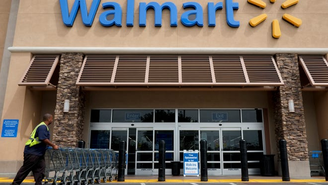 In this May 9, 2013, file photo, a worker pushes shopping carts in front of a Wal-Mart store in La Habra, Calif.  Wal-Mart Stores Inc. enjoyed accelerated business at its core U.S. namesake stores in the fourth-quarter, Tuesday, Feb. 21, 2017,  as it drew more shoppers, encouraging signs that its efforts to lower prices and beef services are helping to gain inroads against online leader Amazon.com.
