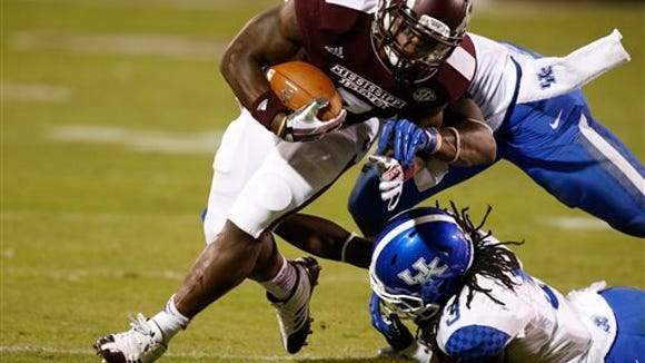 Mississippi State running back Nick Griffin (7) is tripped by Kentucky cornerback Fred Tiller (3) and defensive end Alvin Dupree in the second half of their NCAA college football game at Davis Wade Stadium in Starkville, Miss., Thursday, Oct. 24, 2013. Mississippi State won 28-22. (AP Photo/Rogelio V. Solis)