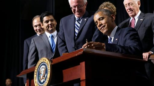 President Barack Obama, flanked by Senate Veterans Affairs Committee Chairman Sen. Bernie Sanders, I-Vermont (left) and House Minority Whip Steny Hoyer of Maryland (right), signs H.R. 3230, the Veterans? Access to Care through Choice, Accountability, and Transparency Act of 2014, Thursday at the Wallace Theater in Fort Belvoir, Va. The bill gives resources to the Department of Veterans Affairs to improve access and quality of care for veterans.