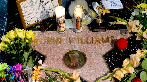 """Flowers are placed in memory of actor/comedian Robin Williams on his Walk of Fame star in the Hollywood district of Los Angeles Monday. Williams, a brilliant shapeshifter who could channel his frenetic energy into delightful comic characters like """"Mrs. Doubtfire"""" or harness it into richly nuanced work like his Oscar-winning turn in """"Good Will Hunting,"""" died Monday in an apparent suicide. He was 63."""