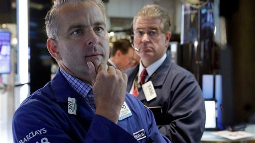 Specialist Christopher Culhane, left, studies a screen at his post, on the floor of the New York Stock Exchange, Thursday, July 3, 2014.  U.S. stock futures headed lower early Friday as a handful of big companies posted weaker results than Wall Street expected. Amazon's shares sank after it posted a quarterly loss.