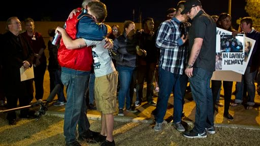 In this Tuesday, Feb. 17, 2015, photo, Robert Meyers, left, receives a hug during a candlelight vigil for his wife, Tammy, who was taken off life support on Saturday after a shooting in Las Vegas. What police first described as a road rage-inspired shooting of an innocent mother of four has morphed into a more complex scenario, prompting a backlash Wednesday against the Las Vegas family and the way the case is being handled.