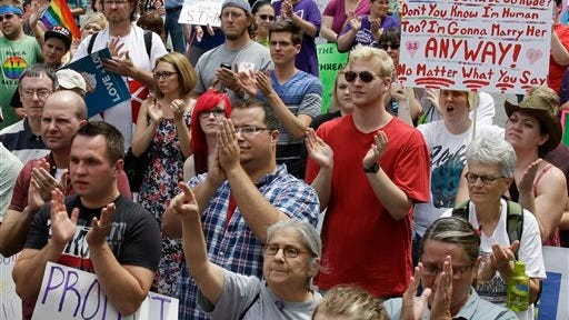 Gay marriage supporters rally on Fountain Square, Wednesday, Aug. 6, 2014, in Cincinnati. Three judges of the 6th U.S. Circuit Court of Appeals in Cincinnati are set to hear arguments Wednesday in six gay marriage fights from four states, Kentucky, Michigan, Ohio and Tennessee. (AP Photo/Al Behrman)