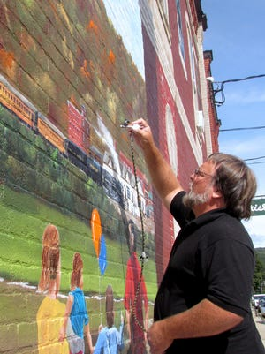Artist Brett Steeves of  Hammondsport works on a mural depicting Corning history on the outside of Brick House Brewery on Corning's Northside.