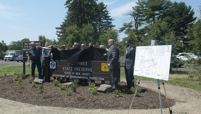 Department of Environmental Protection Commissioner Bob Martin and officials from the New Jersey State Park Service unveil a new sign during a dedication ceremony Monday for Tall Pines State Preserve.