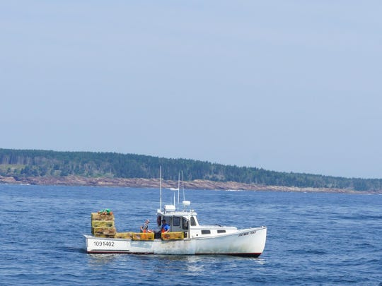 A lobster boat heads toward Monhegan Harbor in Maine.