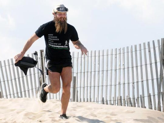 Josh Seehorn sprints over a dune at Cape Henlopen State Park and heads for a dip in the Atlantic Saturday to end his 4,800-mile hike across the American Discovery Trail – a journey Josh began last March to raise support and awareness for the North American Envirothon.