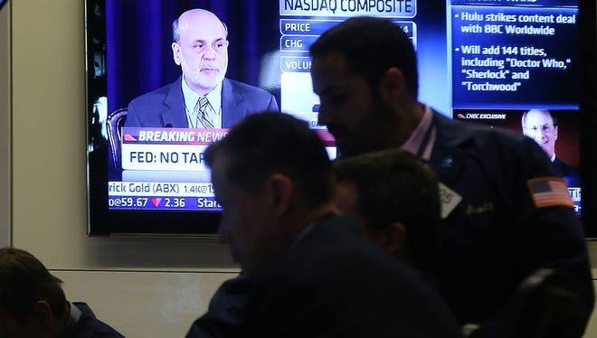 Federal Reserve Chairman Ben Bernanke, speaking at a news conference Wednesday, is seen on a television screen on the floor of the New York Stock Exchange.