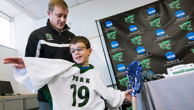 York College men's lacrosse head coach Brandon Childs, top, helps Mitch Pollock put on his jersey at York College Monday.