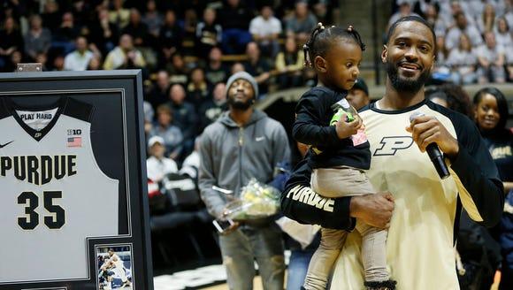 Senior Rapheal Davis holds his daughter Kyndal as he