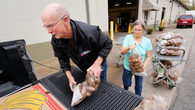 Volunteers Mike and Patty Godlove load a pickup with potatoes, apples and other produce recently at Food Finders Food Bank Warehouse. Food Finders is a United Way partner agency.