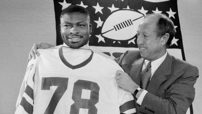 Bruce Smith of Virginia Tech gets fitted for his new jersey by NFL commissioner Pete Rozelle, in New York, in this April 30, 1985 file photo. The Buffalo Bills chose  Smith as the top pick in the draft. Story on jersey retirement: http://on.rocne.ws/1XlOAVq