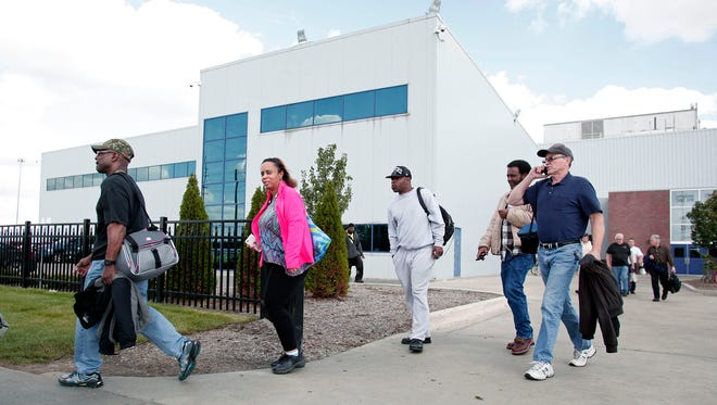 Fiat Chrysler Automobile workers exit from the Warren Truck Assembly Plant at the end of their shift October 7, 2015 in Warren, Michigan.