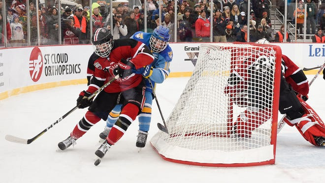 St. Cloud's Lars Olson and St. Cloud Cathedral's Mack Motzko battle for the puck behind the goal during the first period Saturday, Jan. 20, during Hockey Day Minnesota at Lake George.