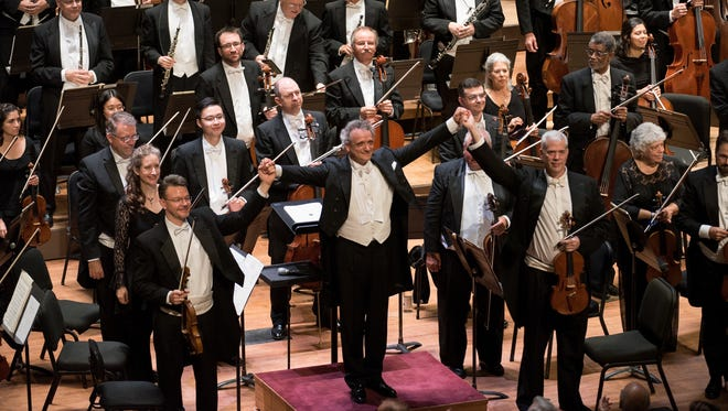 Maestro Louis Langree (on podium) raises the hands of concertmaster Timothy Lees (left) and principal violist Christian Colberg (right) during bows at the gala concert on Oct. 6, 2017, reopening Music Hall after a $143 million renovation.