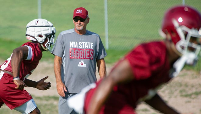 New Mexico State University Head Coach Doug Martin watches as the team runs drills during the first day of practice on Sunday, July 29, 2018 at the Aggie practice fields.