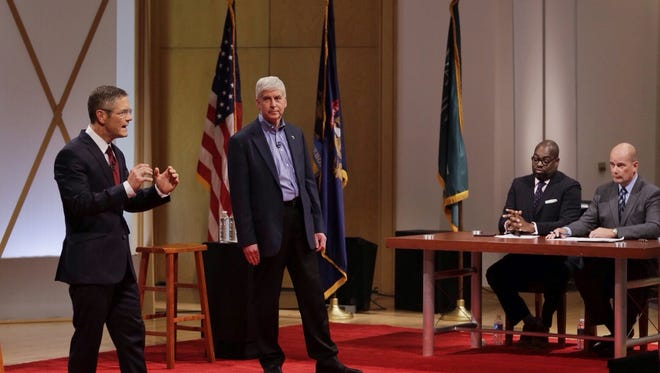 Republican Gov. Rick Snyder and Democratic challenger Mark Schauer, left talk during their town hall meeting at Wayne State University on Sunday, Oct. 12, 2014.