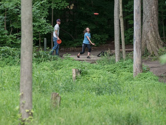 Chelsie Huz and Ryan Derry must toss their discs through standing trees to reach the basket.