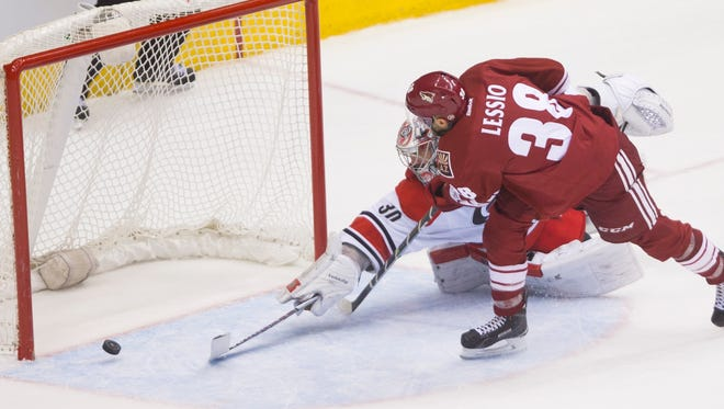 Coyotes' Lucas Lessio (38) beats Hurricanes' Cam Ward but has the puck hit the post and go out during the shoutout at Gila River Arena in Glendale on Feb. 5, 2015.