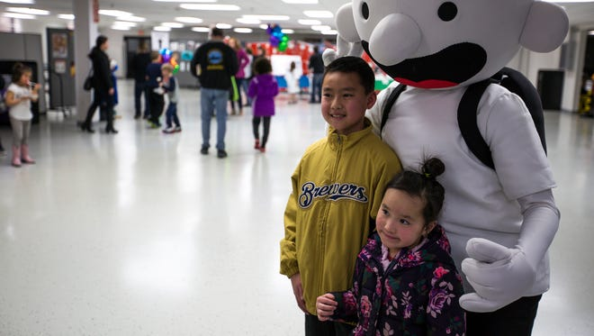 """Fans pose for photos with """"Diary of a Wimpy Kid"""" main character Greg Heffley during an event at Worzalla Publishing in Stevens Point, Wis., April 10, 2018. The series' author Jeff Kinney made an appearance at the publishing company, which has published his series since its first installment in 2007, to celebrate 200 million copies sold worldwide."""