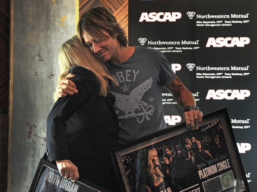 "Keith Urban gets a hug from Cindy Mabe, president of UMG Nashville, which encompasses the EMI, Capitol, Mercury and MCA labels, as they celebrated the No. 1 song ""We Were Us"" at Music City Tippler on Monday, Aug. 25, 2014, in Nashville. ""We Were Us"" is Urban's 16th No. 1 song."