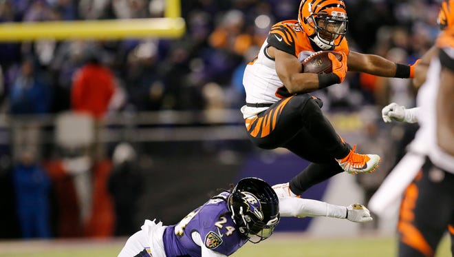 Cincinnati Bengals running back Giovani Bernard (25) leaps over a tackle attempt from Baltimore Ravens cornerback Brandon Carr (24) on a carry in the fourth quarter of the NFL Week 17 game between the Baltimore Ravens and the Cincinnati Bengals at M&T Bank Stadium in Baltimore on Sunday, Dec. 31, 2017. The Bengals won 31-27 in the regular season finale.