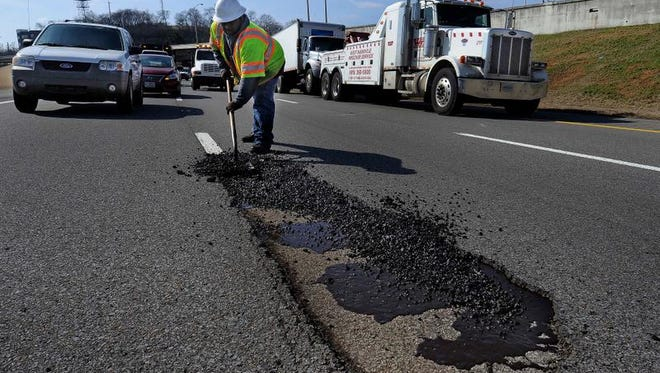 A TDOT worker fills in a pothole Monday in Nashville. The holes have pocked interstates after the recent snow and ice.