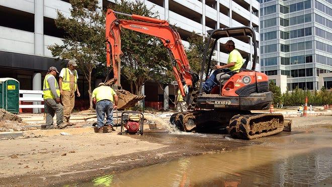 Works repair a water main break on Capitol Street in downtown Jackson, Miss.