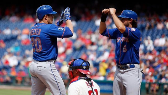 New York Mets' Anthony Recker, left, and Matt den Dekker, right, celebrate over Philadelphia Phillies catcher Carlos Ruiz after Recker's three-run home run during the seventh inning of a baseball game, Monday, Aug. 11, 2014, in Philadelphia. New York won 5-3.