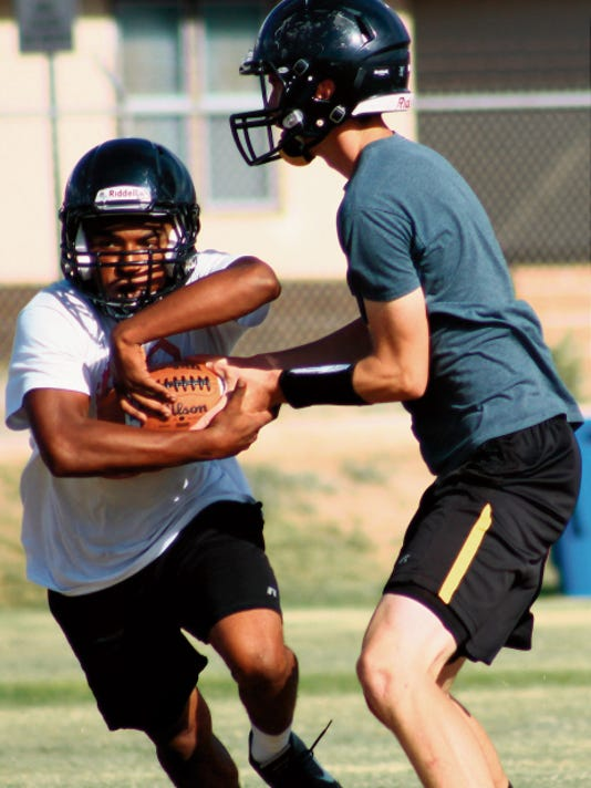 Kyle Hooper hands off to Carlos Hicks during practice Monday at the Alamogordo High School practice field.