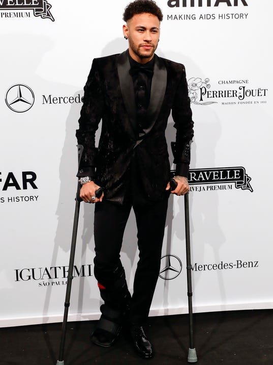 Brazilian soccer player Neymar poses on the red carpet of The Foundation for AIDS Research (amfAR) event in Sao Paulo, Brazil, Friday, April 13, 2018. (AP Photo/Andre Penner)